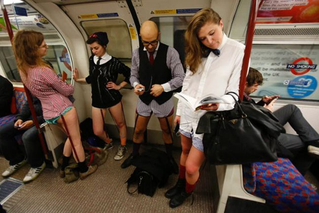 epa04017265 People take part in a No Pants Day 2014 flash mob on the London Underground, in London, Britain, 12 January 2014. The event is organized by Improv Everywhere and takes place in many cities across the world. The goal for the participants is to get on public transport dressed in normal winter clothes, but without pants while keeping a straight face. EPA/TAL COHEN